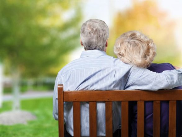 an elderly couple sitting on a park bench
