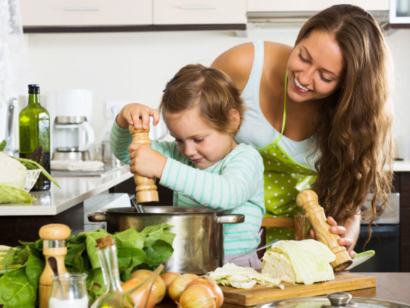 a child and mother cooking in the kitchen